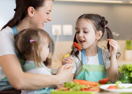 Child tasting food during cooking with their mother