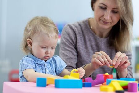 Mom and child playing with developmental toys. Early education concept.