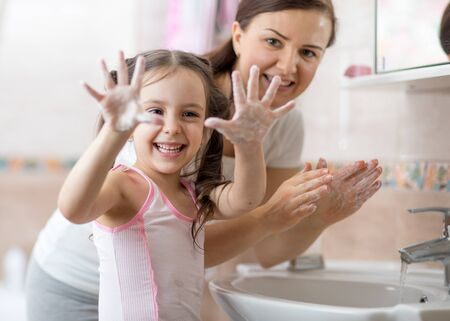 Kid washing hands and showing soapy palms Imagens