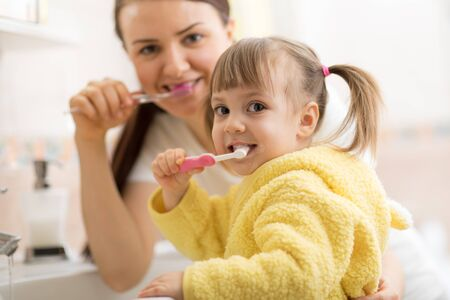 Smiling child kid with her mom brushing and clean teeth in bathroom