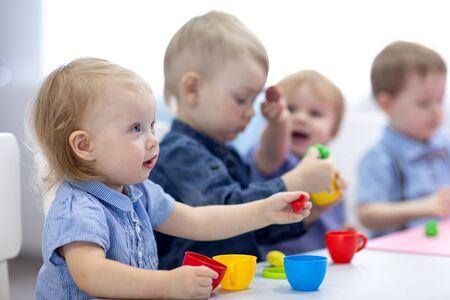 groupe d'enfants jouant avec de l'argile de jeu à la crèche ou à la maternelle ou à la garderie