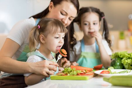 Mom with daughters chopping vegetables in domestic kitchen
