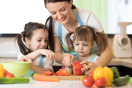 Mum with daughters chopping vegetables in home kitchen