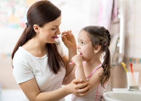 Mother teaches her little daughter accurately teeth brushing Stock Photo - 137323663