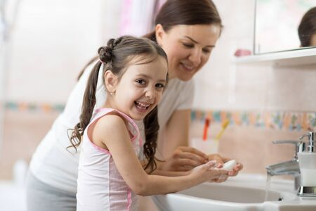 Woman and her daughter child girl washing hands with soap in bathroom