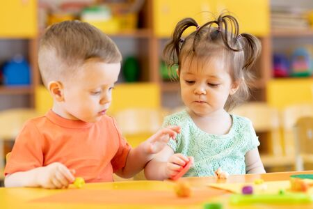 Toddlers boy and girl playing at table with educational toys. Children infants at home or daycare.