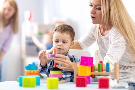 mother and her baby son building toy pyramid tower Imagens