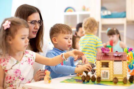 Kids play toys in kindergarten. Group of preschool kids on lesson in class