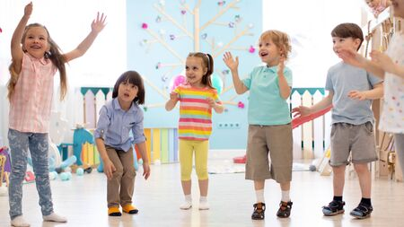 Cheerful kids stand semicircle on floor in kindergarten or day care centre. Preschoolers have fun indoors, playing games Imagens