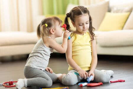 Funny kids play doctor with toy tools. Children sitting on floor in living room