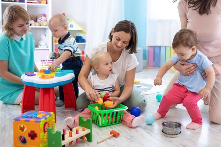 Group of moms have a fun pastime with their kids in playroom