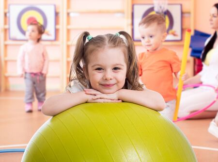 Smiling pretty child with fitness ball in gym