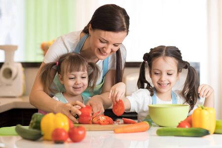 Happy mother and kids cooking and cutting vegetables on kitchen Stockfoto