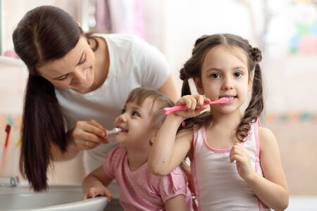 Happy family in bathroom. Mom teaches teeth brushing her younger daughter Imagens
