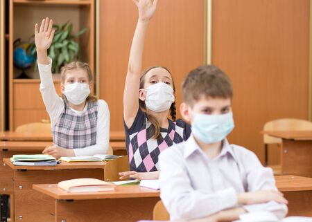 Schoolers wearing protection mask to prevent virus on lesson in classroom
