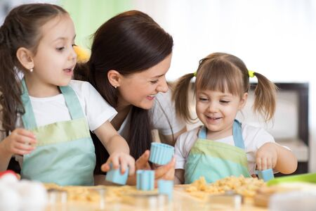 Mom and her cute little daughters are playing and joying while baking in kitchen at home