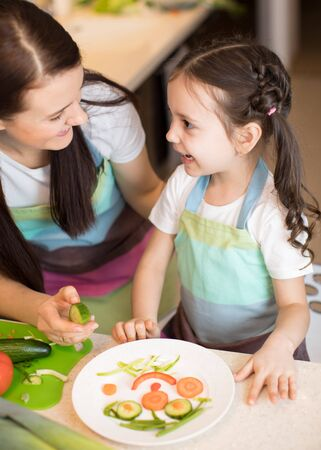 Happy mother and her kid enjoy making healthy meal together at their kitchen Imagens