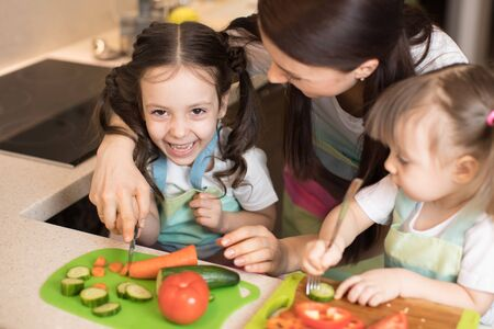 Happy mother and her kids enjoy making healthy meal together at their home