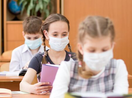 Schoolkids with medicine mask on faces against virus in classroom