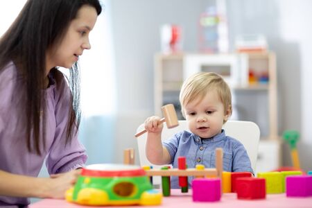 Mother and child son playing with educational toys together at home