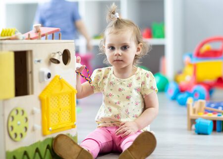 Cute toddler baby playing with busy board in daycare. Childrens educational toys. Archivio Fotografico