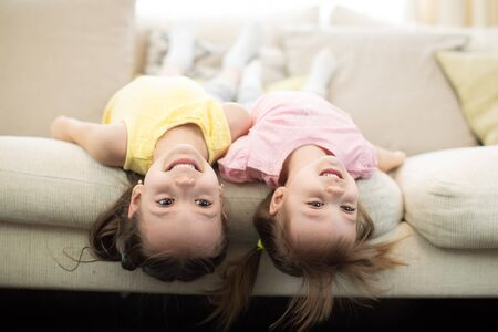 Portrait of little girls laughing lying upside down. Cheerful kids sisters having fun on sofa at home Imagens