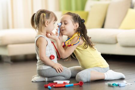 Children play doctor and hospital using toy medical tool having fun at home