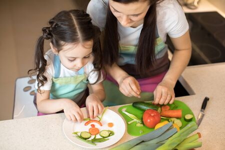 Cute mom and her kid making funny face from vegetables Imagens