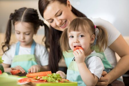 Positive family preparing lunch in the kitchen Imagens