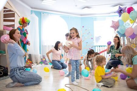 Little kids and parents have fun on children birthday party Imagens