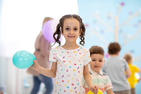 Kid girl with balloon on children party background Imagens