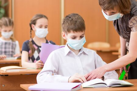 school children with protective masks against coronavirus at lesson in classroom