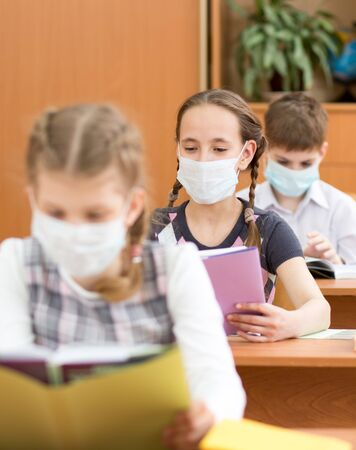 School kids with protective mask on faces against virus in classroom