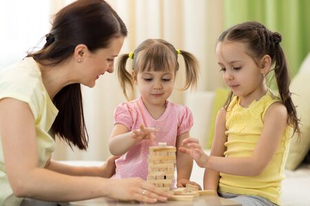 Mother with kids play board game in living room. Family spending time together at home