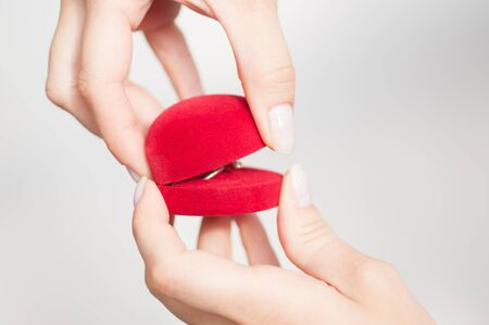 Red gift box in the form of heart with a ring inside in female hands on a white background shot with natural light