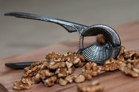 tongs for chopping walnuts and shelled walnut close up