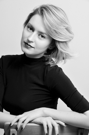 studio portrait of a blonde girl with a short haircut of European appearance in a black dress