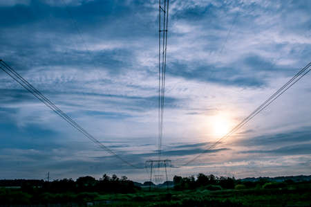 high-voltage line against the blue sky outside the city