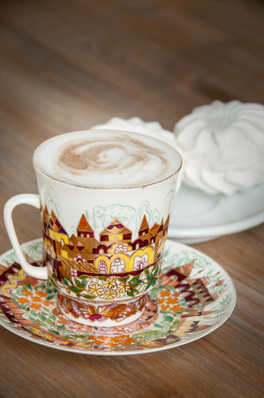 bright cup of cappuccino coffee with marshmallow close-up