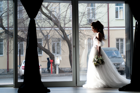 Bride in a white wedding dress with a christmas bouquet of flowers closeup
