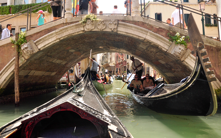 Venice canals in Italy, bridges, tourists and gondoliers in the summer on a sunny day, Venice, Italy June 28, 2011