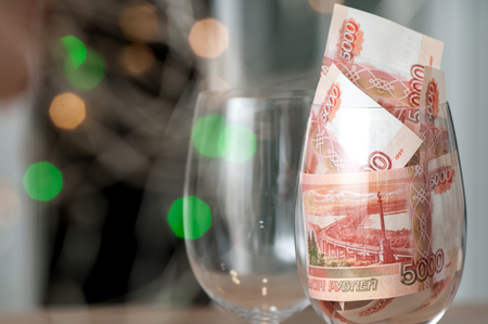 Russian banknotes in a glass. Christmas background. Close-up.