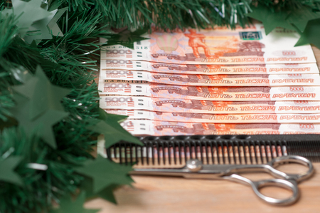 Russian bills with a hairdressing tool. Christmas background