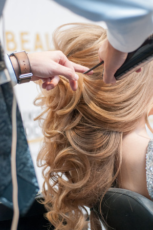Process of evening creating hairstyles for a girl with long blond hair by a master hairdresser at a beauty marathon in Chelyabinsk, Hotel Redisson Blue, December 2, 2018