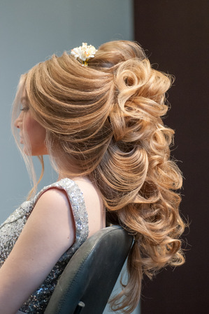 evening hairstyle on a model girl with long blond hair and in an evening white dress at a beauty marathon in Chelyabinsk, Hotel Redisson Blue, December 2, 2018