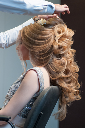 Process of creating hairstyles for a girl with long blond hair by a master hairdresser at a beauty marathon in Chelyabinsk, Hotel Redisson Blue, December 2, 2018