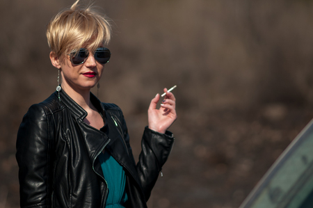 girl with a short haircut and blond hair with a cigarette in her hands on the street close-up