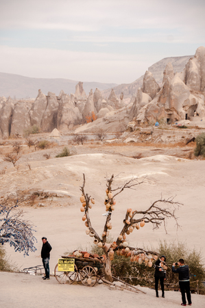 Cappadocia, Turkey November 13, 2016:People against a volcanic landscape and a tree with hanging souvenirs in Cappadocia in the fall sunny day Imagens