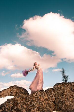 Ragazza la bionda in un vestito lungo rosa in cima alla montagna contro il cielo e le nuvole Archivio Fotografico