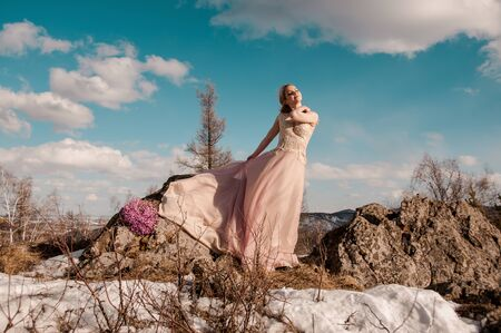 Girl the blonde in a pink long dress on top of the mountain against the sky and clouds